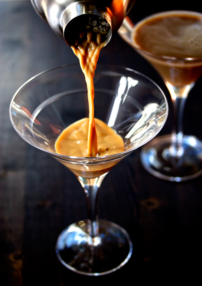 pouring the mixed espresso, vodka and baileys into a martini glass
